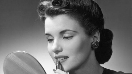 Woman applying lip-stick